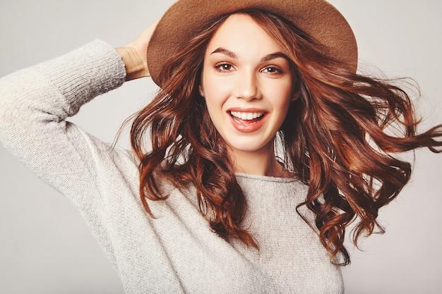 Портрет молодой стильной смеющейся модели в серой повседневной летней одежде в коричневой шапочке с натуральным макияжем