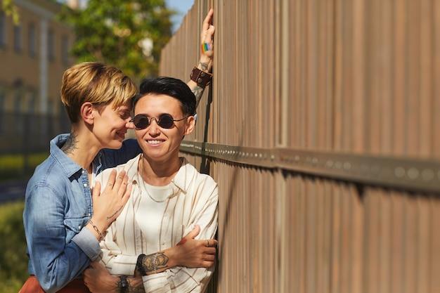 夏の日に屋外に立って笑顔の若いスタイリッシュなレズビアンの肖像画