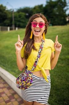 都市公園で楽しんでいる若いスタイリッシュな女性の肖像画、陽気な気分、ポジティブ、感情的な笑顔、黄色のトップ、ストライプのミニスカート、ハンドバッグ、ピンクのサングラス、夏のスタイルのファッショントレンドを身に着けている