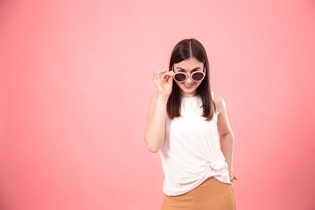 Портрет молодой стильной женщины в солнечных очках с улыбкой на лице на розовом фоне изолировал космос экземпляра.