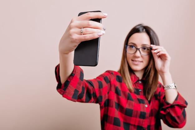 本当の感情で孤立した壁に自分撮りを作る若いスタイリッシュな女性の肖像画。孤立した壁にスマートフォンを使用して現代の女性