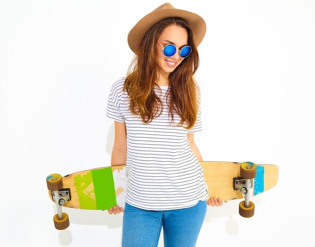 Портрет молодой стильной модели женщины в повседневной летней одежде в коричневой шляпе, позирующей с longboard столом. изолированные на белом