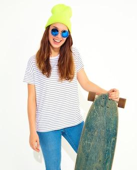Портрет молодой стильной женской модели в повседневной летней одежде в желтой шапочке позирует с longboard стол. изолированные на белом