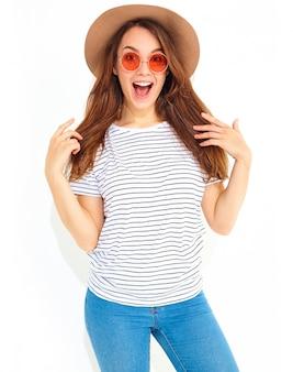 白い壁に分離された自然なメイクと茶色の帽子でカジュアルな夏服で驚きの表情を持つ若いスタイリッシュな女性モデルの肖像画。カメラ目線