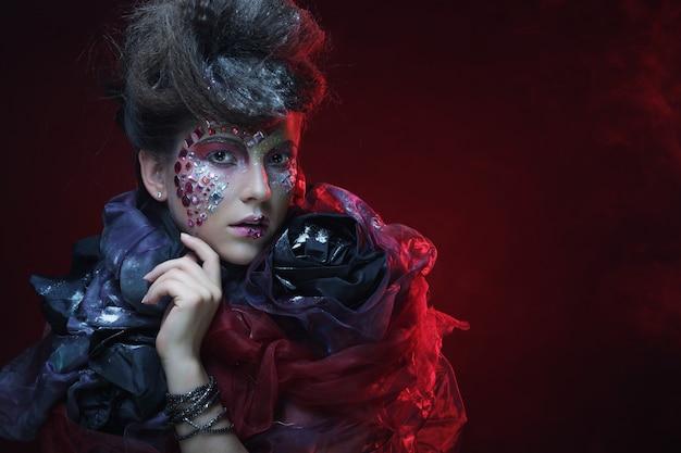 赤い背景の上の創造的な顔を持つ若い様式の女性の肖像画