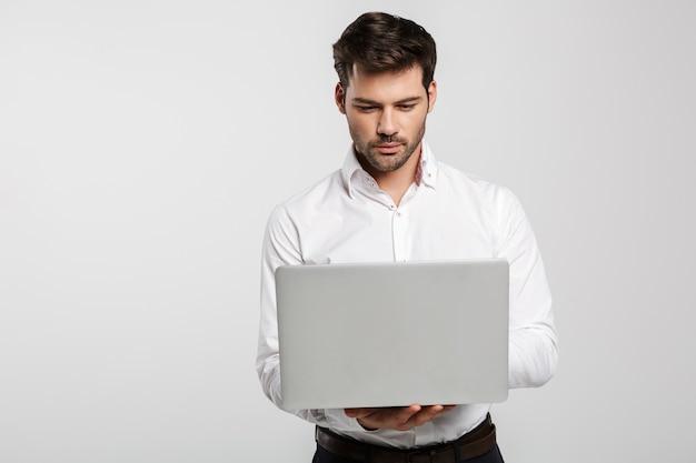 Портрет молодого успешного бизнесмена, держащего и использующего ноутбук, изолированного на белом