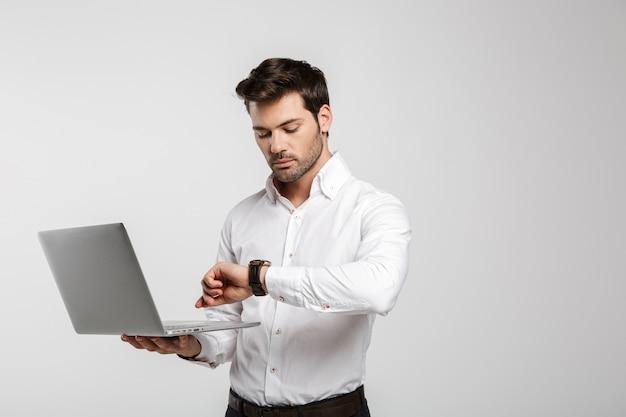 Портрет молодого успешного бизнесмена, держащего ноутбук и смотрящего на наручные часы, изолированные на белом