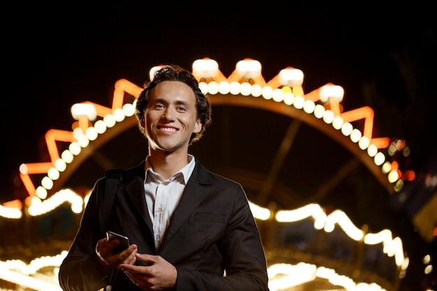 夜の遊園地で若い成功した実業家の肖像画。浅い自由度