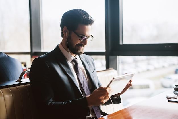 明るい窓の近くのモダンなカフェでタブレットから音楽を聴くスーツで成功したハンサムなひげを生やした若いビジネスマンの肖像画。