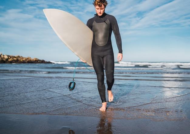 彼の腕の下にサーフボードで水を離れる若いサーファーの肖像画。スポーツとウォータースポーツのコンセプト。