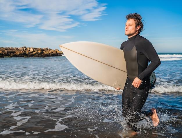 Портрет молодого серфера, выходящего из воды с доской для серфинга под мышкой