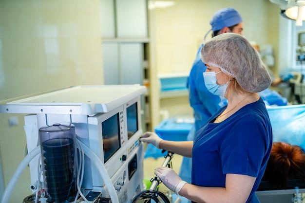 手術室に立っているスクラブで若い外科看護師の肖像画。現代の医療室の女性医師の肖像画。