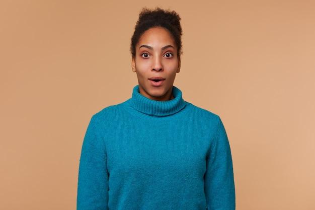 巻き毛の黒い髪の青いセーターを着ている若い驚いたアフリカ系アメリカ人男性の肖像画。ベージュの背景の上に隔離された目を大きく開いてカメラを見てください。