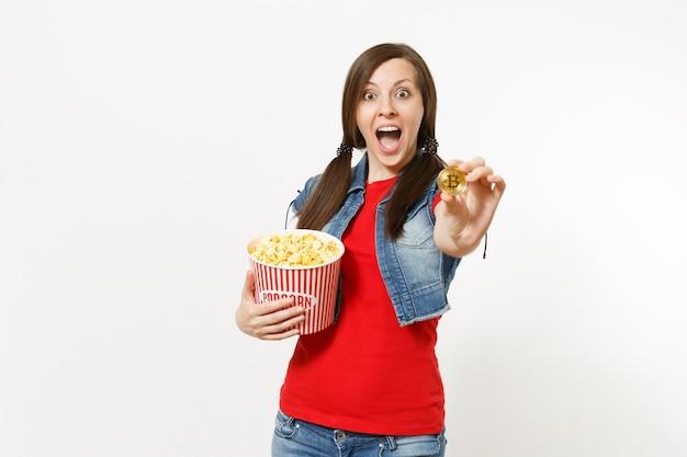 흰색 배경에 격리된 팝콘과 비트코인 양동이를 들고 영화 영화를 보고 있는 캐주얼한 옷을 입은 젊은 놀란 매력적인 브루네트 여성의 초상화. 영화 개념의 감정.