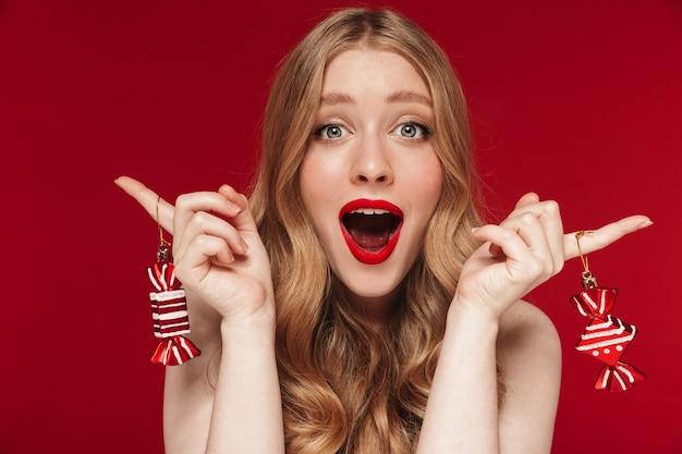 크리스마스 사탕 장난감을 들고 밝은 빨간 립스틱으로 빨간 벽에 고립 된 포즈를 취하는 젊은 백인 여자의 초상화.