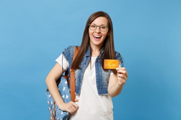 デニムの服、青い背景で隔離のクレジットカードを保持しているバックパックとメガネの若い驚きの興奮したきれいな女性の学生の肖像画。高校大学カレッジコンセプトの教育。