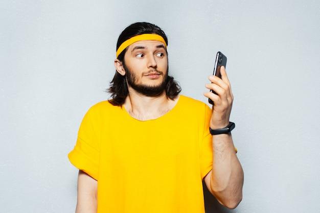 灰色の壁の背景に黄色い服を着て、スマートウォッチを使用して、スマートフォンで見て驚いた若い男の肖像画。