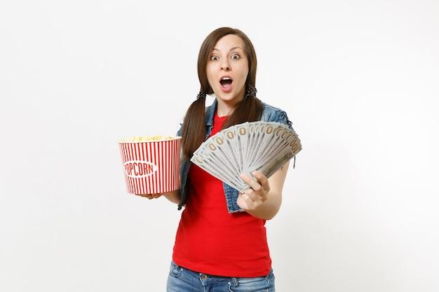 팝콘 양동이와 달러 묶음, 흰색 배경에 격리된 현금 돈을 들고 영화를 보고 있는 캐주얼한 옷을 입은 젊고 놀란 예쁜 여성의 초상화. 영화 개념의 감정.