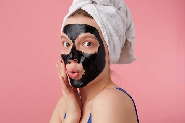 Портрет молодой удивленной женщины после душа с полотенцем на голове, с черной маской, трогает лицо, с шокированным выражением лица, стоит.