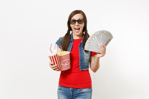 3d 안경을 쓰고 팝콘 양동이, 탄산음료 또는 콜라 한 컵, 달러 묶음, 흰색 배경에 격리된 현금을 들고 영화를 보고 있는 놀란 젊은 여성의 초상화. 영화 속 감정.
