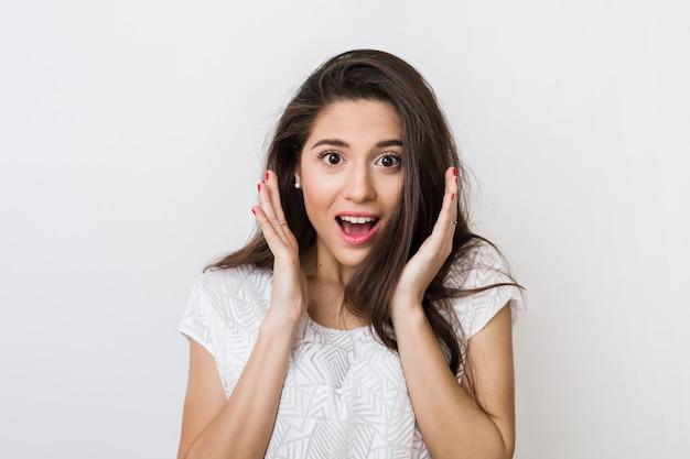Портрет молодой удивленной женщины в белой блузке с длинными волосами, позитивным выражением шокированного лица, счастливой, держащей руки вверх на ее лице,