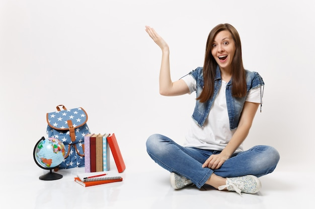 손을 옆으로 가리키는 데님 옷을 입은 놀란 젊은 여학생의 초상화, 지구본, 배낭, 고립된 학교 책 근처에 앉아