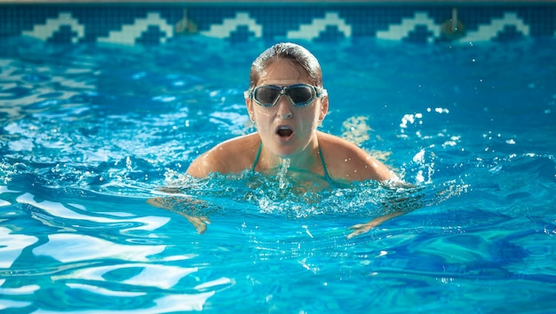 Портрет молодой женщины пловца, переводя дыхание в бассейн