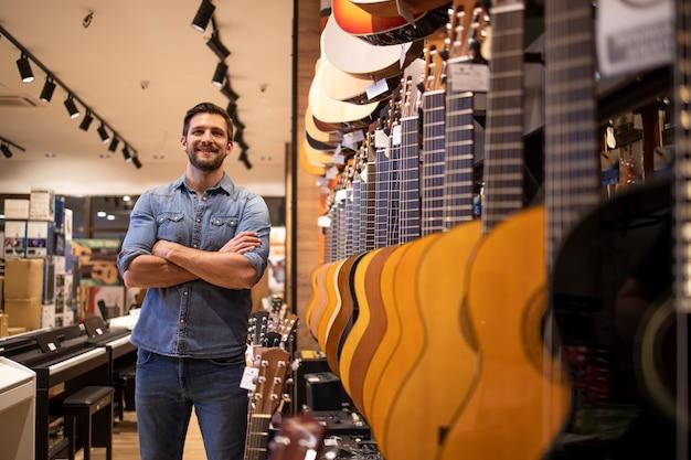 Портрет молодого талантливого музыканта, стоящего в музыкальном магазине у большой коллекции гитарных инструментов.