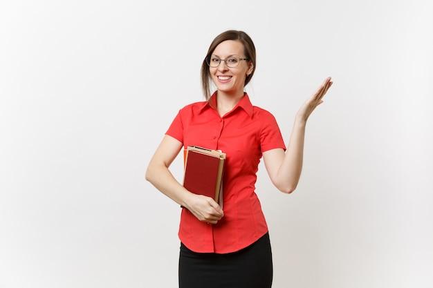 Портрет молодой женщины учителя в красной рубашке, юбке и очках, держа книги, указывая рукой в сторону на космосе экземпляра, изолированном на белой предпосылке. образование или преподавание в концепции университета средней школы.