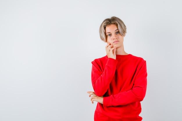 赤いセーターで頬に指を保持し、動揺した正面図を見て若い十代の少年の肖像画
