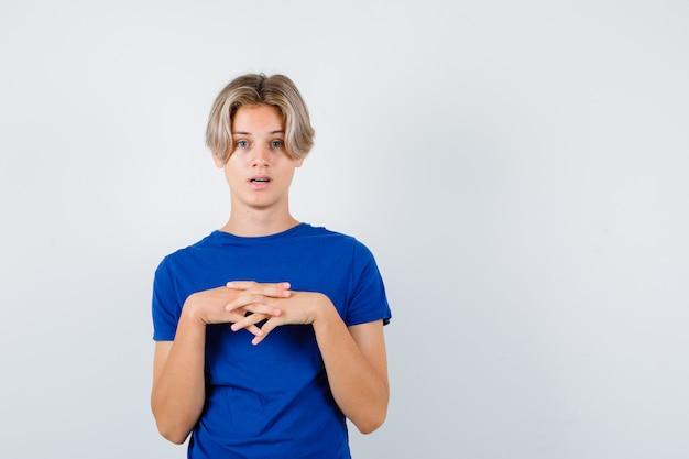 파란색 티셔츠를 입은 가슴에 얽힌 손가락을 들고 혼란스러운 앞모습을 바라보는 어린 10대 소년의 초상화