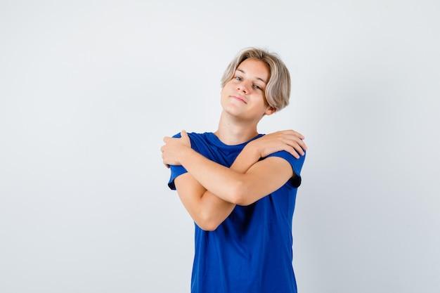 파란색 티셔츠를 입고 자신을 껴안고 자랑스러운 앞모습을 바라보는 어린 10대 소년의 초상화