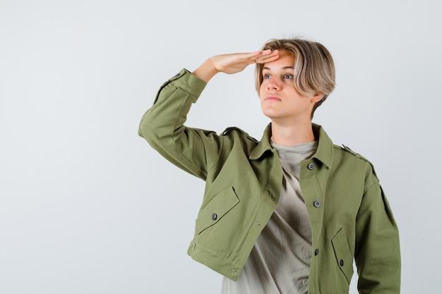 Портрет молодого мальчика-подростка, смотрящего далеко с рукой над головой в зеленой куртке и смотрящего сфокусированным видом спереди