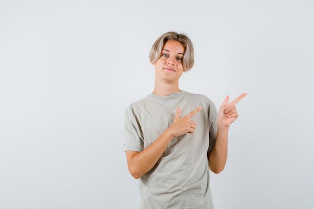 Tシャツの右上隅を指して陽気な正面図を見て若い10代の少年の肖像画
