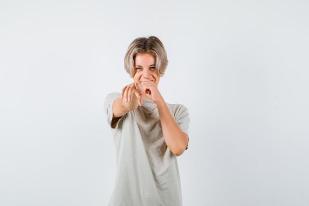 前方を向いて、tシャツで口に手を保ち、幸せな正面図を見て若い10代の少年の肖像画