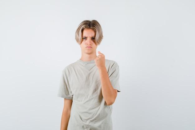 Портрет молодого мальчика-подростка, показывающего сжатый кулак в футболке и смотрящего в ярости, вид спереди