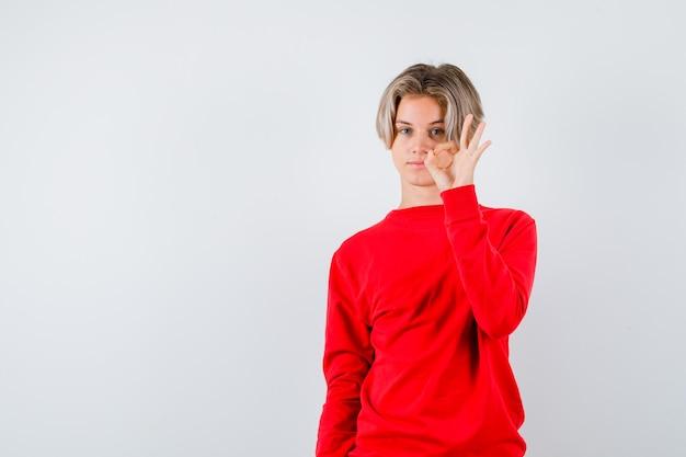 赤いセーターでokジェスチャーを示し、満足している正面図を見て若い10代の少年の肖像画