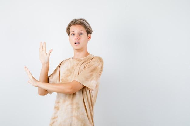 Портрет молодого мальчика-подростка, показывающего жест стоп в футболке и выглядящего испуганным, вид спереди