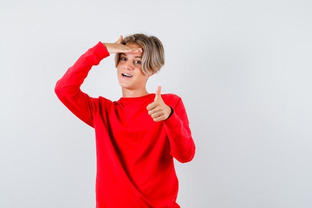 赤いセーターと陽気な正面図を頭の上に手で親指を上に表示している若い十代の少年の肖像画