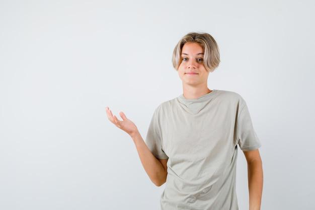 티셔츠에 손바닥을 옆으로 펼치고 쾌활한 앞모습을 바라보는 어린 10대 소년의 초상화
