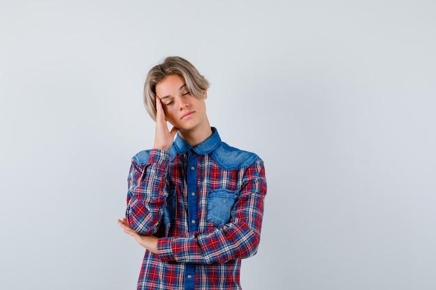 Портрет молодого мальчика-подростка, страдающего от головной боли, в клетчатой рубашке и усталого вида спереди