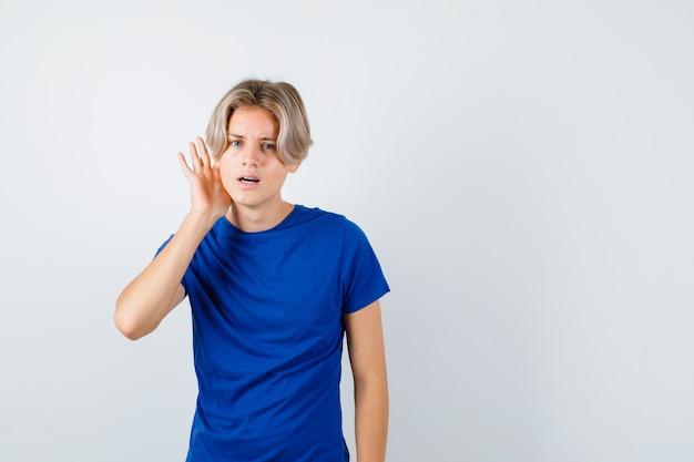파란색 티셔츠를 입고 귀 뒤에 손을 얹고 혼란스러운 앞모습을 보고 있는 어린 10대 소년의 초상화