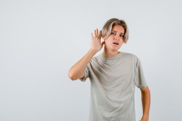 티셔츠를 입고 귀 뒤에 손을 얹고 혼란스러운 앞모습을 보고 있는 어린 십대 소년의 초상화