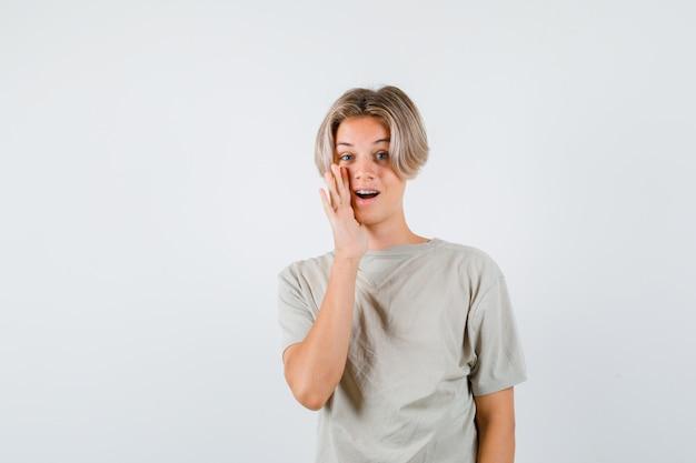 Tシャツの口の近くに手と不思議な正面図を見て若い10代の少年の肖像画