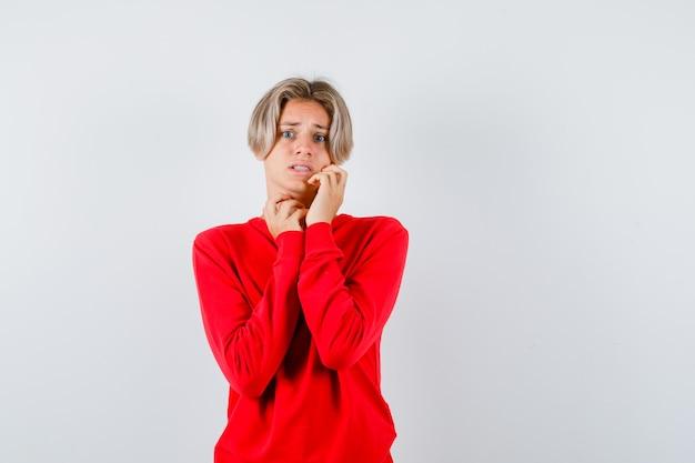 빨간 스웨터를 입은 뺨에 손을 대고 겁에 질린 정면을 바라보는 어린 십대 소년의 초상화