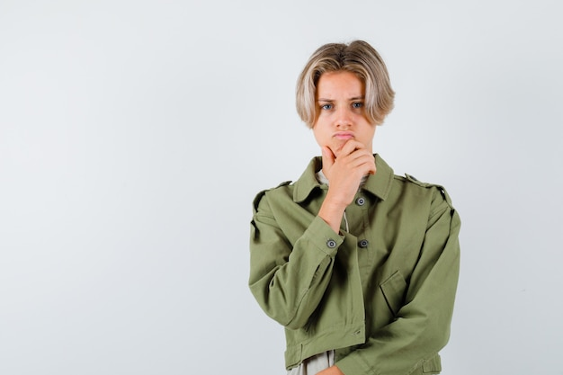 Портрет молодого мальчика-подростка с рукой на подбородке в зеленой куртке и угрюмого вида спереди