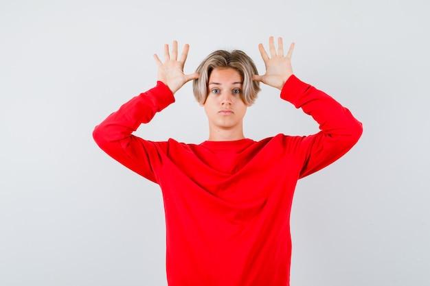 빨간 스웨터를 입은 귀처럼 머리 근처에 손을 대고 어리둥절한 정면을 바라보는 어린 10대 소년의 초상화