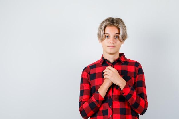 チェックシャツを着て胸に手を持って、希望に満ちた正面図を探している若い十代の少年の肖像画