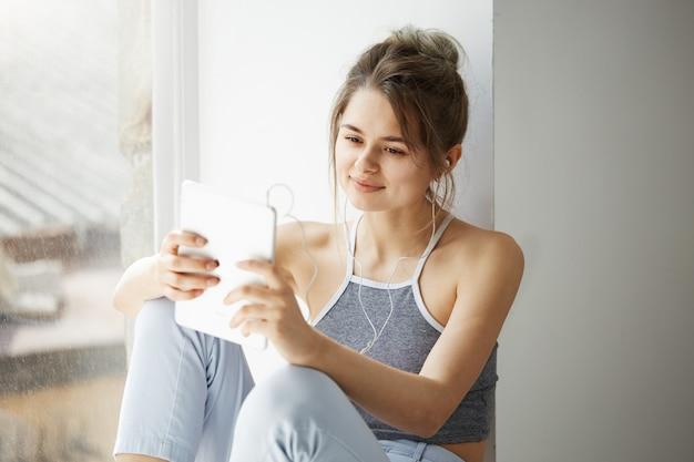 白い壁の上の窓の近くに座ってインターネットを閲覧するタブレットサーフィンwebを見て笑ってヘッドフォンで若い10代の陽気な女性の肖像画。