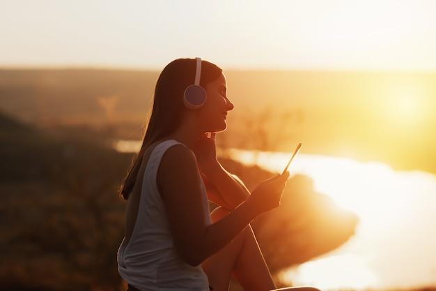 Портрет молодой нежной девушки наслаждается выходными на природе и слушает музыку через наушники.